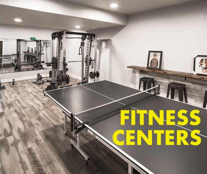 Home gym with exercise equipment and ping-pong table illustrating article about home fitness centers