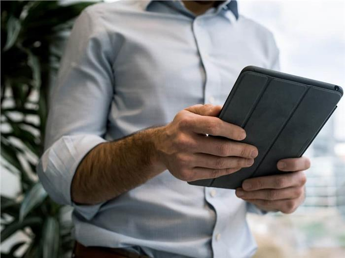 Man working on tablet reviewing work