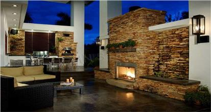 Covered rear patio with seating and stacked-stone fireplace in home with outdoor living features.