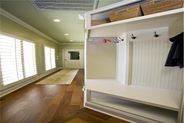 Mudroom in 4-bedroom Country home with white bench, shoe cubbies, coat-hanging area, and shelving.
