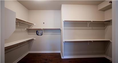 Large white closet with shelving and hanging rods in 3-bedroom Craftsman style home design.