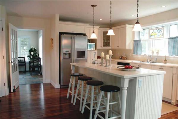 White kitchen island with white countertop and 4 stools in 2-bedroom house design in Country style.