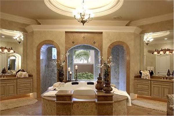 Luxurious master bathroom with two separate vanities, two toilet areas, and a large central shower space.