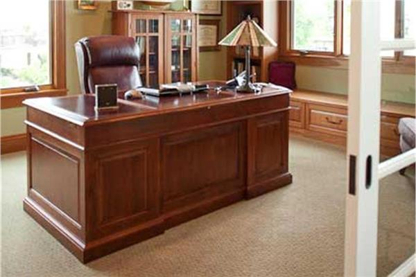 Home office with raised-panel wooden desk and leather office chair, with open French doors.