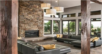 High-ceiling family room with upper transom windows in 5-bedroom Contemporary home design.