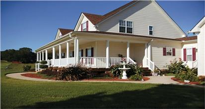 Traditional farmhouse style home with a huge wrap around front porch, spacious deck and screened in porch.