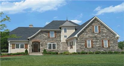 House in the country French architectural style with two stories, stucco and stone exterior and steep rooflines.