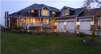 Night view of large Shingle style home plan with white trim and 3-car garage.