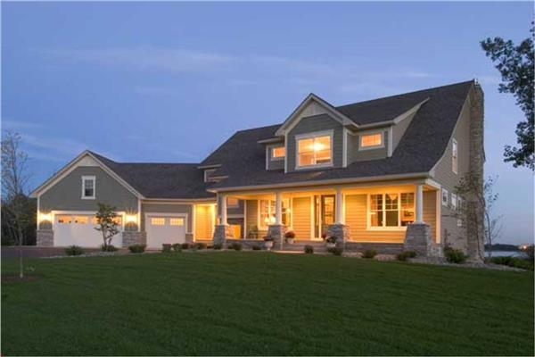 Farmhouse home plan with 3 bedrooms in 3289 sq. ft. shown in evening with lights on.