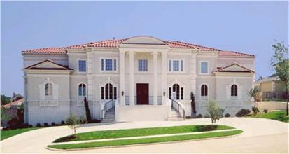 Large white home in the historic architectural style with tall columns in front and arched windows.