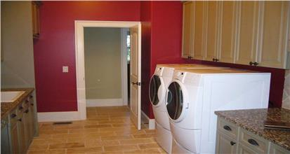Laundry room with large washer and dryer, red walls, cabinets, granite countertops, and sink.