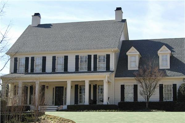 Four-bedroom home in Colonial architectural style with porch, wood siding exterior, and shutters adorning windows.
