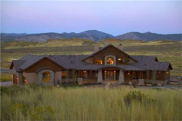 Luxury rustic home design in the Craftsman style with natural wood siding in rural mountain setting.