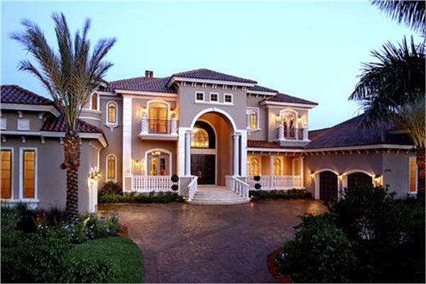 Mediterranean home with two 2-car garages flanking a large paver-style entry courtyard.