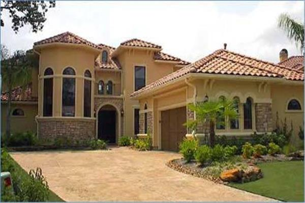 Luxurious Mediterranean style house with arched openings, stucco-and-stone exterior, and red tile roof.