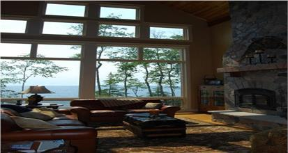 Two-story Great Room in view lot home with stone fireplace and a wall of windows looking out on the water.