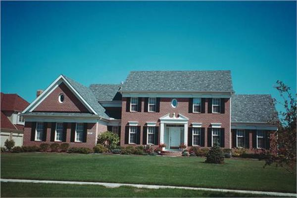 4-bedroom, 2957-sq.-ft. Colonial style home design with brick siding, portico with white columns, and black shutters.