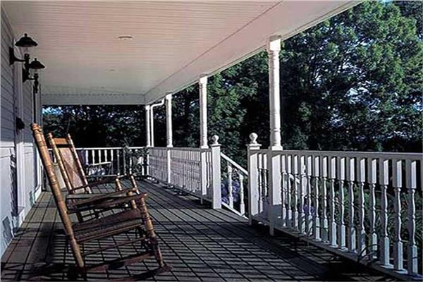 Long porch, with white railings and wooden rocking chairs, on Country Farmhouse style house.