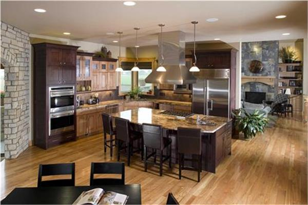 Beautiful modern kitchen with light and dark wood cabinets and large center island with cooktop and 4 chairs.