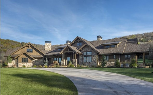 Sprawling Ranch style home with stone exterior siding, exposed wood timbers, and steep roof