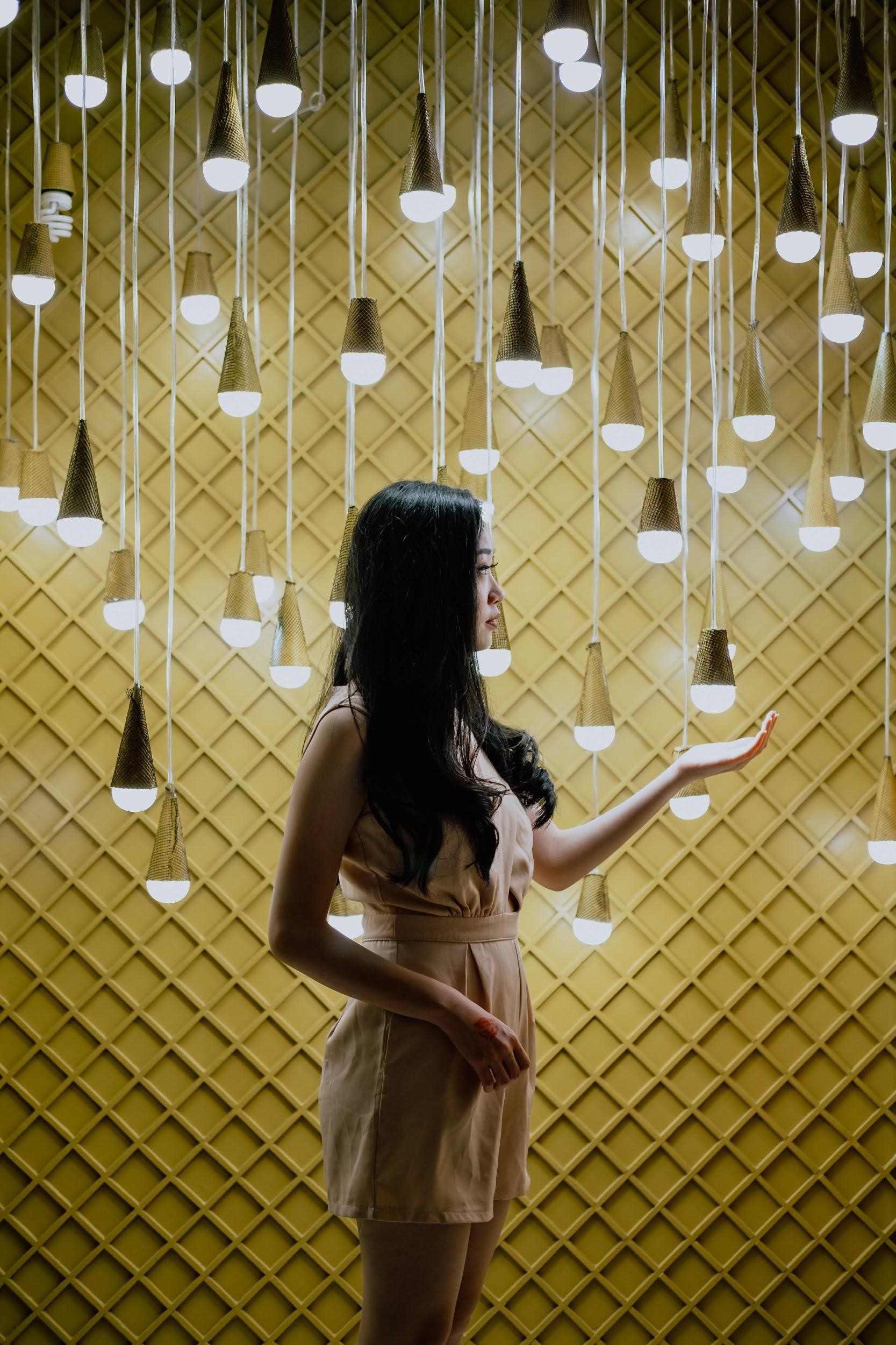 Woman among lightbulbs that can controlled from an iPhone