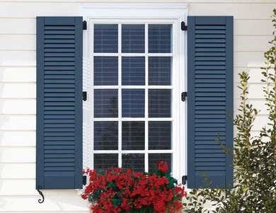 Dark louver window shutters against a white background