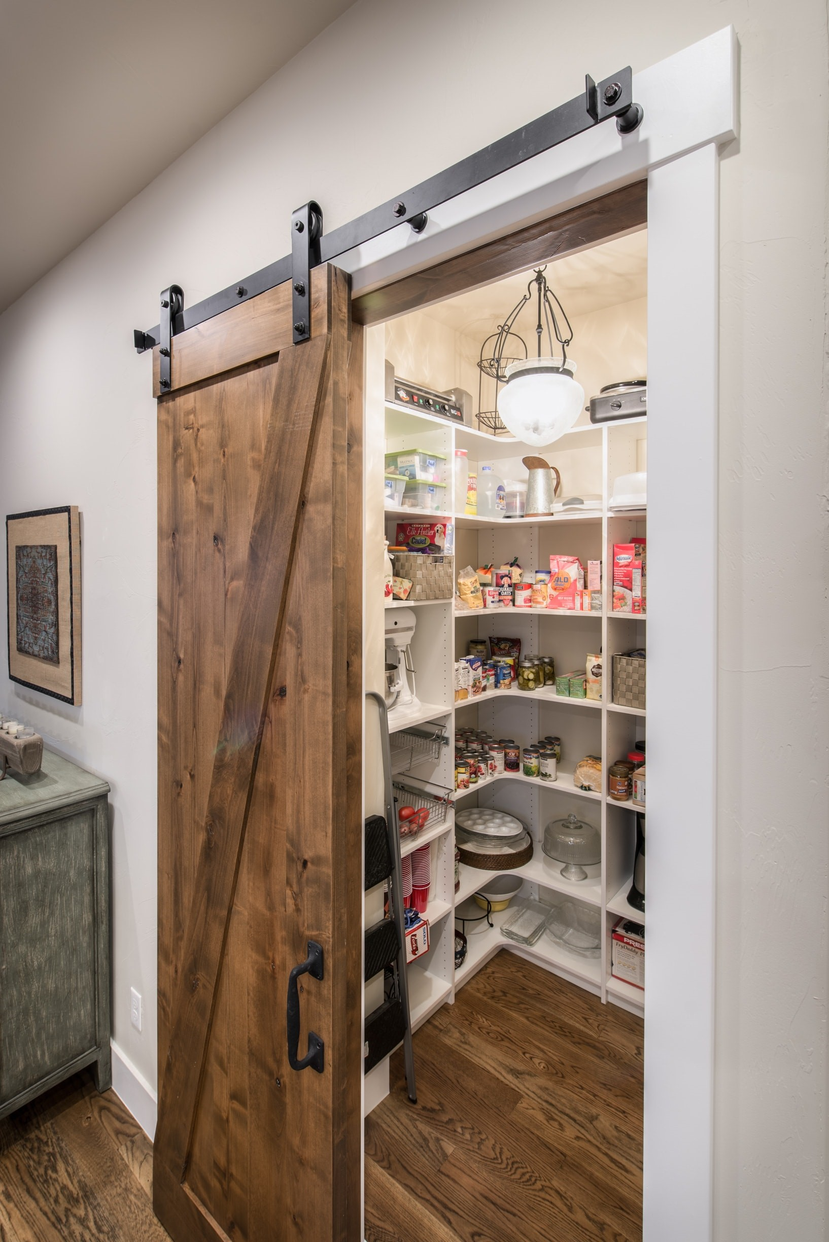 Sliding wooden barn door reveals a walk-in kitchen pantry in house plan #161-1072