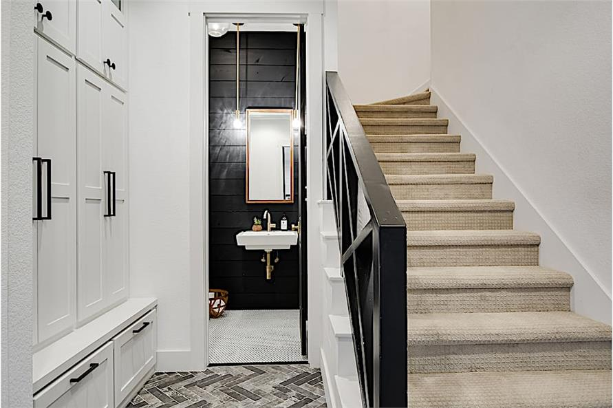 Powder room with black wall and white wall-hung sink
