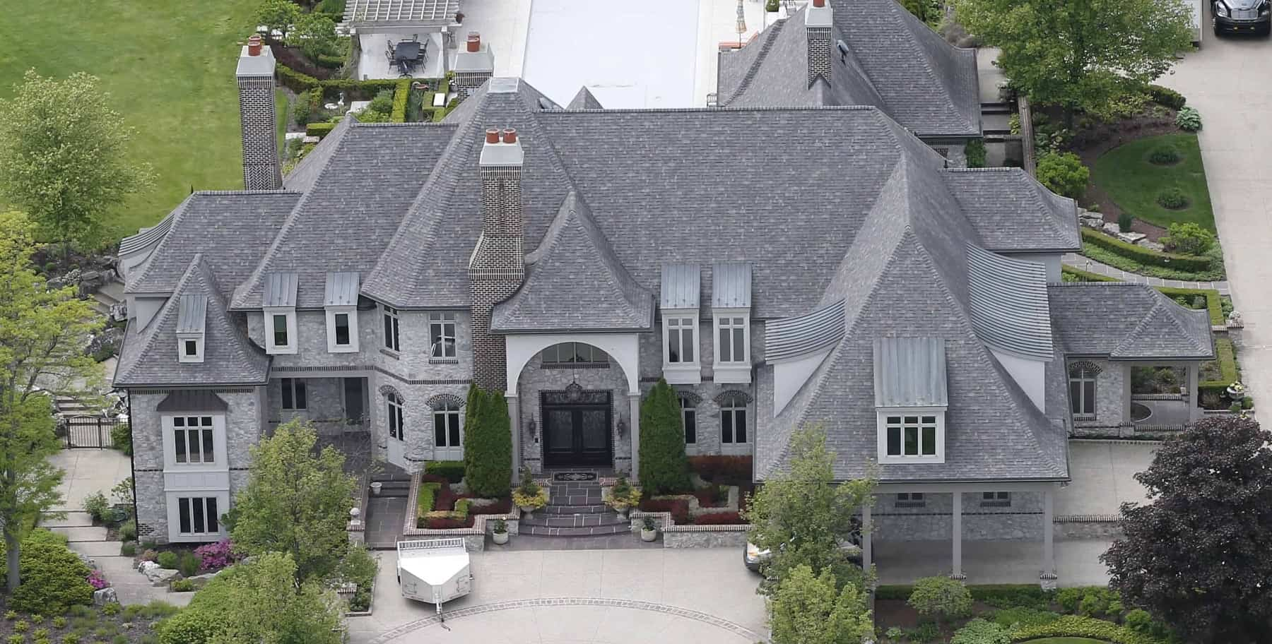 Large European or French Chateau style home with stone siding