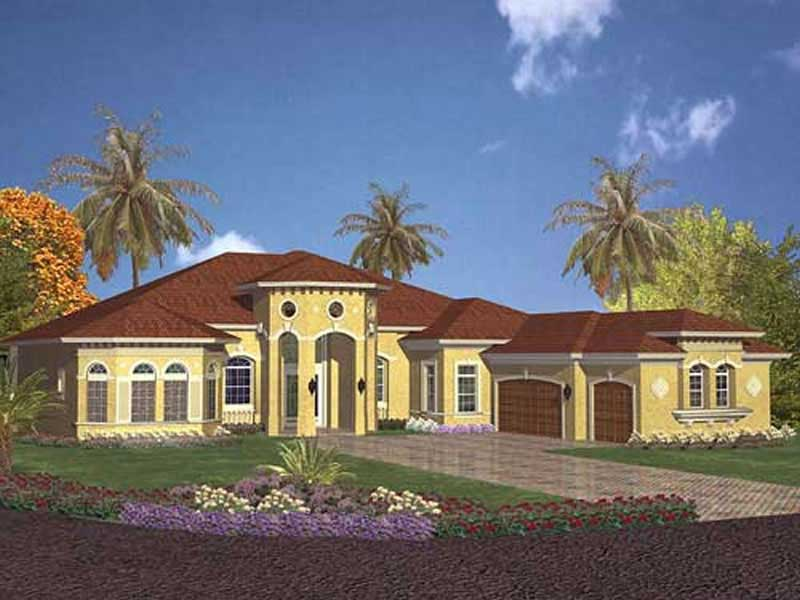 Beige stucco Spanish style home with round windows in front