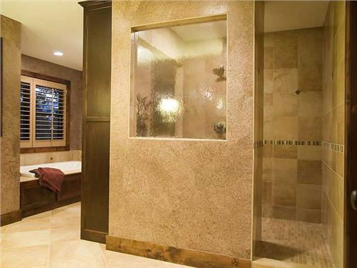 Modern looking bathroom with walk-in shower land lots of tile and stone