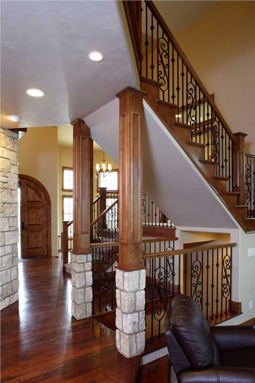 Beautiful foyer with perfect use of stone, wood and iron detailing for the stairway.