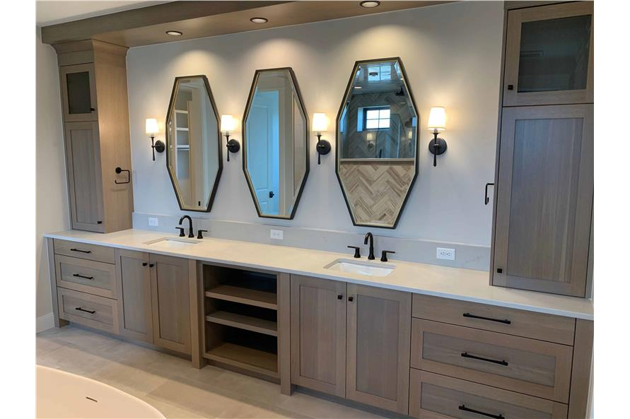 Bathroom with natural wood cabinets and three octagonal mirrors