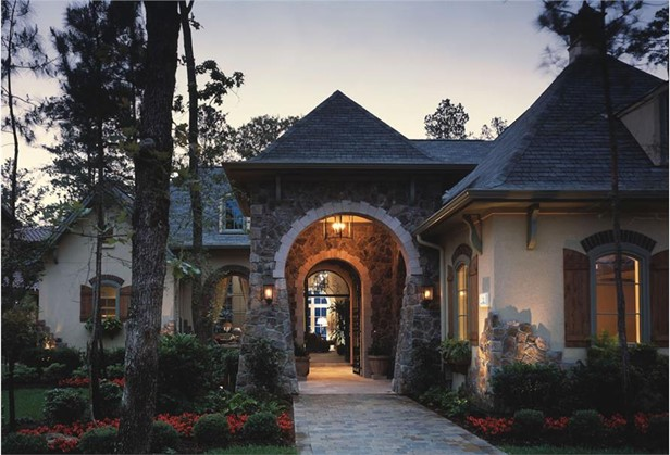 Landscaped courtyard lined with plants and flowers, plus a welcoming front porch with an arched entryway