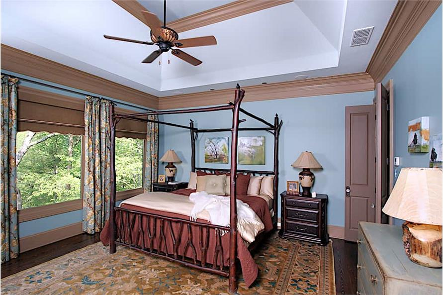 Rustic style canopy bed in master suite with natural wood accents