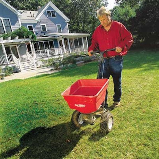 Fertilizing a home lawn with a walk-behind spreader