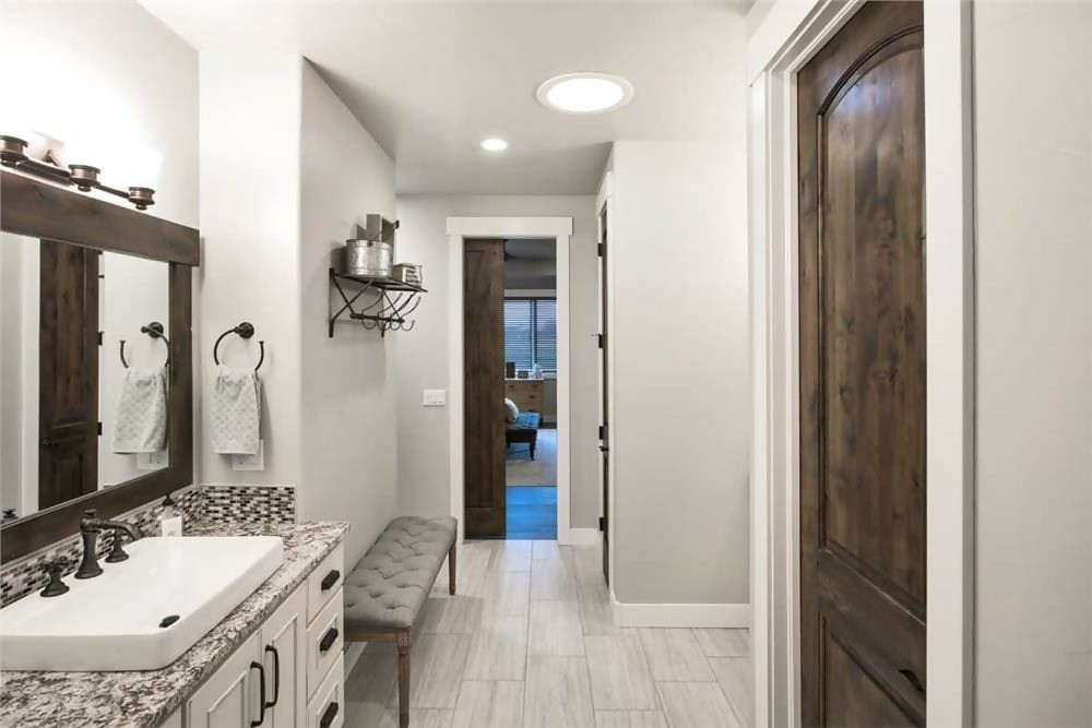 Light, neutral-colored bathroom with extra-wide plank flooring made of porcelain tile
