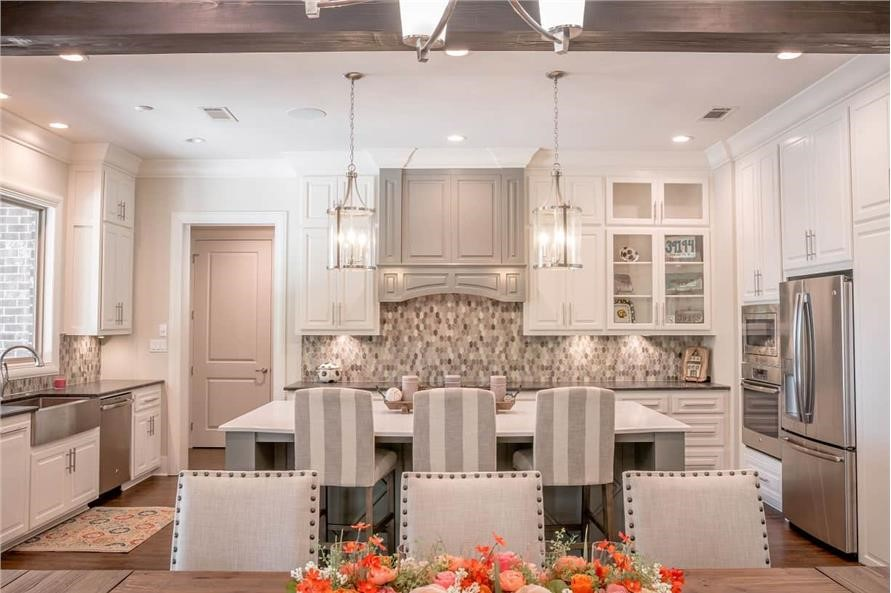 Bright white kitchen with stainless-steel farmhouse apron sink and appliances