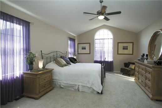 Master bedroom with vaulted ceiling and curtains that add a pop of color