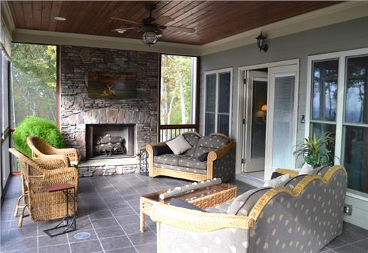 Screened porch with rock and stone fireplace perfect for an outdoor living area.