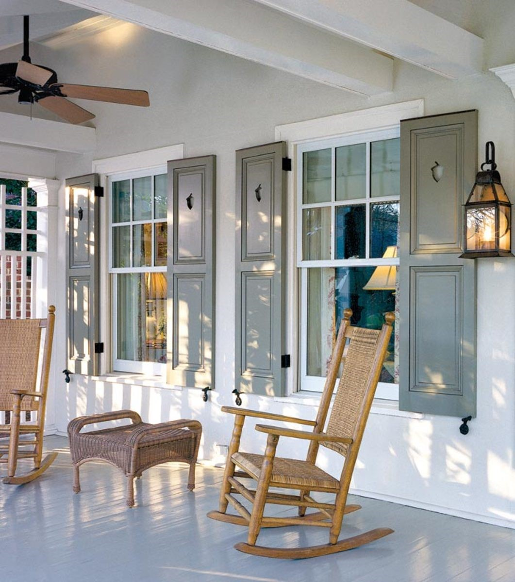 Porch with natural wood rocking chairs and sage-color window shutters