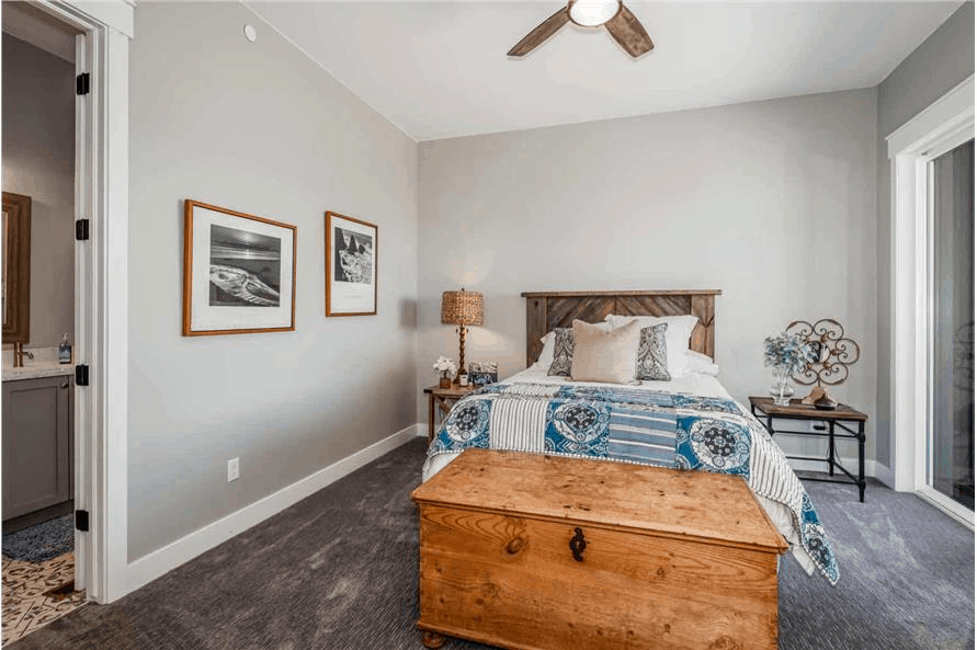 Bedroom decorated in blue solids and patterns with footboard chest that complements the picture frames