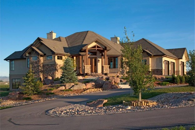Beautiful mountain home in stucco and stone with intricate hip and gable style roof