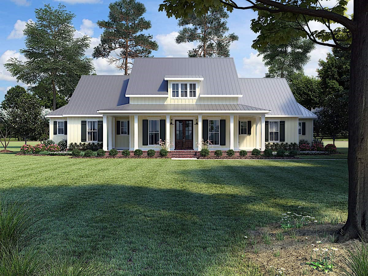 Light yellow-sided Farmhouse style home with white trim and standing-seam metal roof