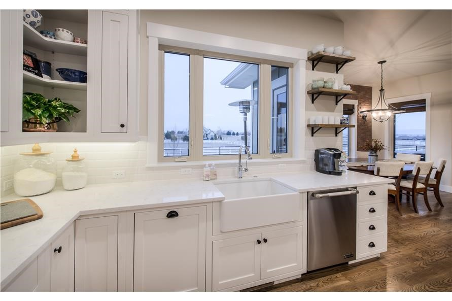 All-white kitchen with farmhouse style sink, stainless-steel appliances, and exposed shelving instead of wall cabinets
