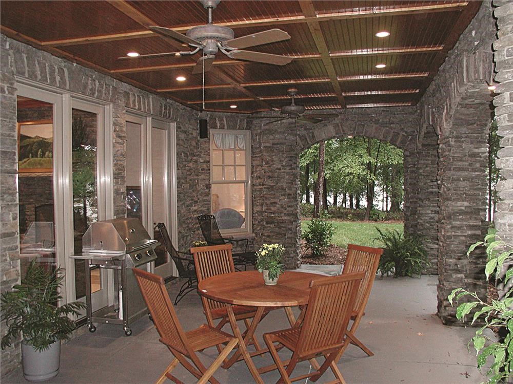 Covered patio with dining table and chairs at the rear of a Country style home