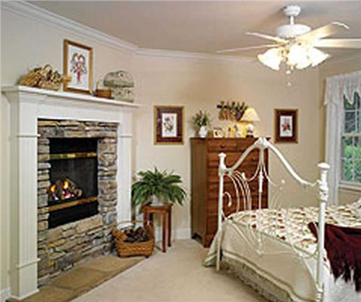 Master bedroom with stacked-stone fireplace and ceiling fan
