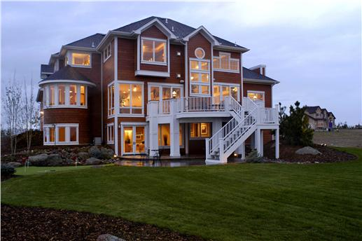 Rear of Shingle style home with windows in all shapes and designst