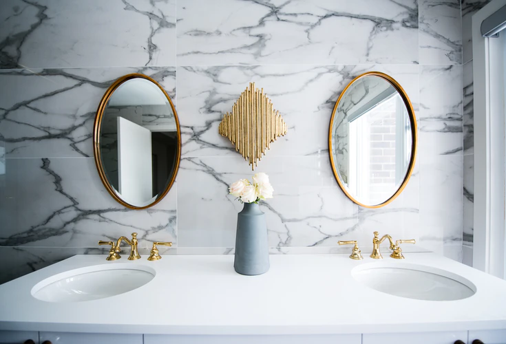 Marble and gold bathroom with twin oval mirrors