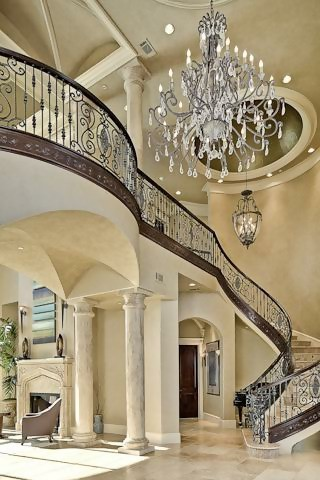 Two-story-tall foyer with elaborate staircase and chandelier